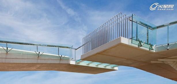 """吻桥联系了城镇两个不同的部分,其不同的跨越方式让每一边的边界都被重新定义。其""""吻""""的含义带来了浪漫主义色彩,让人们用全新的方式来看待这个区域。 以白色混凝土板为材料,其结构设计类似日本折纸艺术,当然,这可不是纸上谈兵。一侧的一字型桥结构悬臂梁达到16米,另外一侧的Y状桥包括一个坡道和一个楼梯。两则的组合加起来,总路径长度超过60米。桥体与下方的雨水通道与45°角交互。两侧相""""吻""""之处由钢梁结构的玻璃地板联系。其结构设计优雅周全。"""